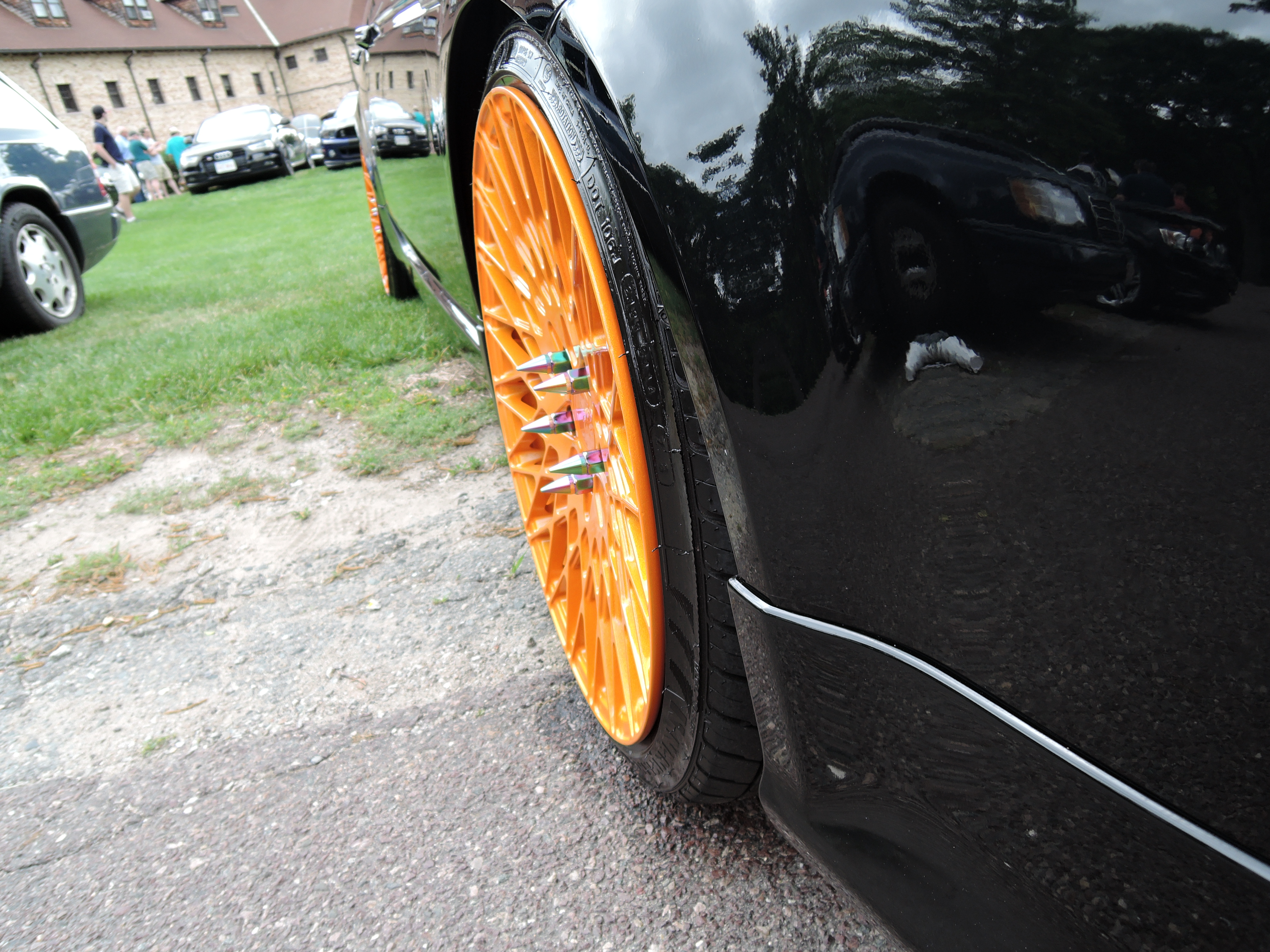 Cars and Coffee Car Show at Lars Anderson; Orange tire rim wheel