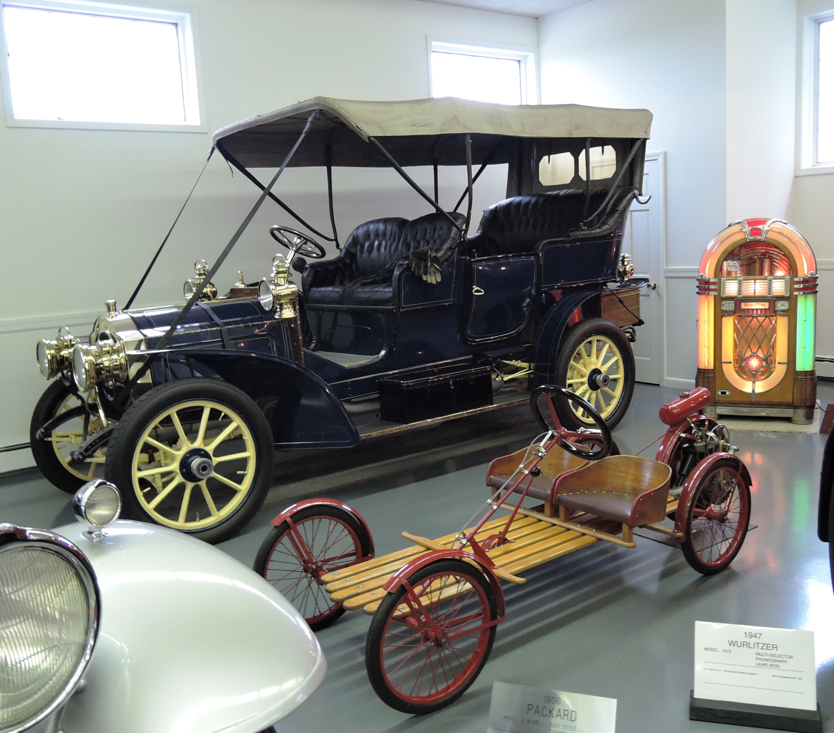 1906 Packard Touring, with a 1947 Wurlitzer Multi-selector Phonograph Jukebox to the right and a 1924 Auto Red Bug Buckboard in front - bahre car collection